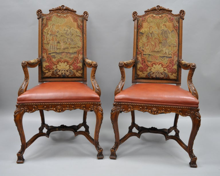 Set of eight Rococo style carved walnut, leather, and needlepoint dining chairs, circa 1900. Set includes two armchairs with figural needlepoint upholstered backs and armrests and leather upholstered seats. The six side chairs having leather