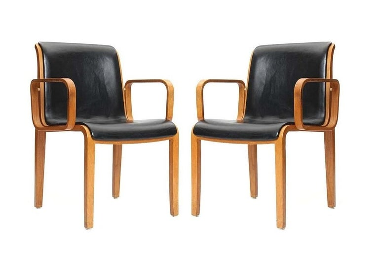 This vintage set of 1300 Series armchairs designed by William 'Bill' Stephens for Knoll. The unique style of Stephens feature gorgeous bent wood with a natural color stain, paired with black upholstery. Marked to underside of frame.