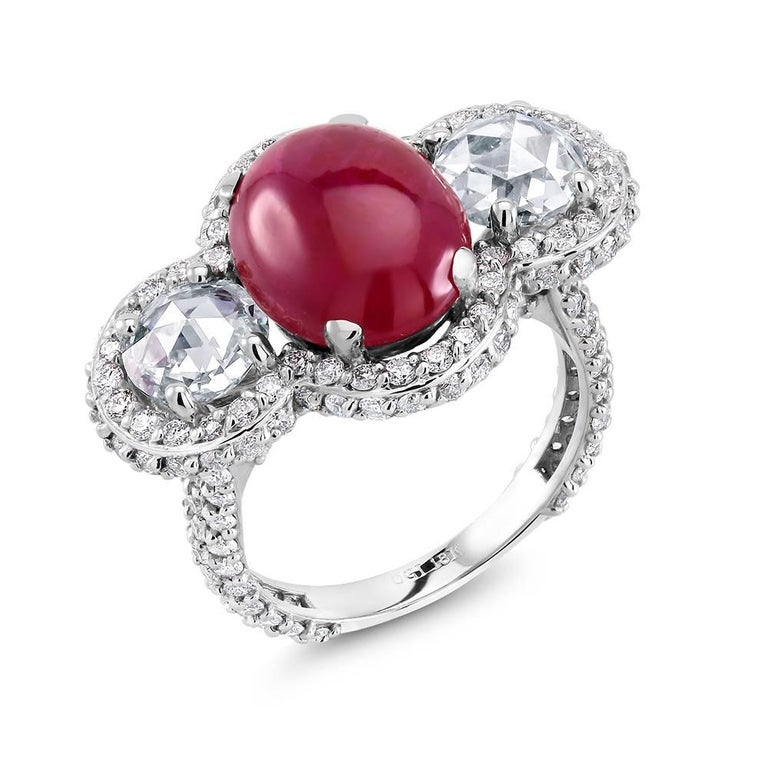 Eighteen karats white gold cocktail cluster ring Burma cabochon ruby weighing 5.85 carats Ruby hue tone color is strawberry red Two old mine diamonds weighing 1.45 carats  Pave set diamonds weighing 2.00 carats Ring size 6.5 In Stock Shank measuring