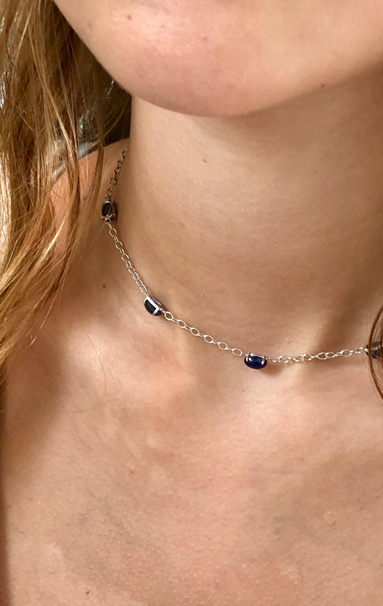 Eighteen karats white gold five cabochon sapphire necklace pendant  Tiny diamond on lobster lock weighing 0.03 carat  Necklace measuring 16 inches long Five cabochon sapphire weighing 9.40 carat Each chain link measuring 0.20