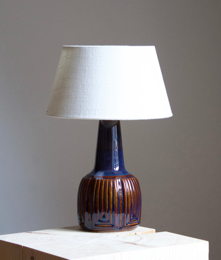 A table lamp produced by Søholm Keramik, located on the island of Bornholm in Denmark. Features a highly artistic glazed and incised decor.   Sold without lampshade. Stated dimensions exclude the lampshade. Height includes socket.  Other