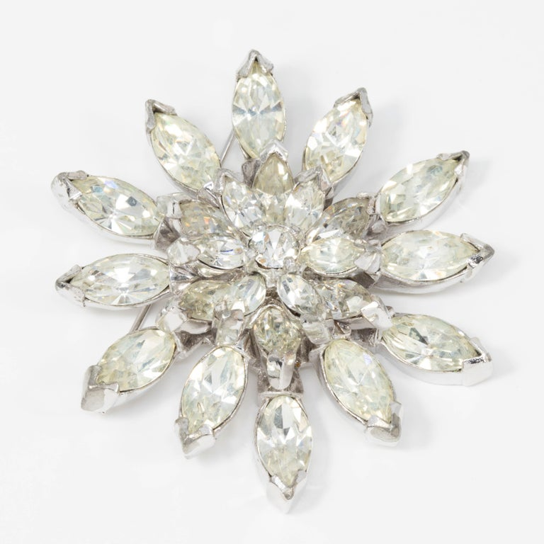 A sparkling pointed petal flower pin brooch from the 1940s Eisenberg Original collection. This glittering accessory features prong-set clear crystals on a silvertone setting, fastened with a pin clasp.  Tags, Marks, Hallmarks: Eisenberg Original