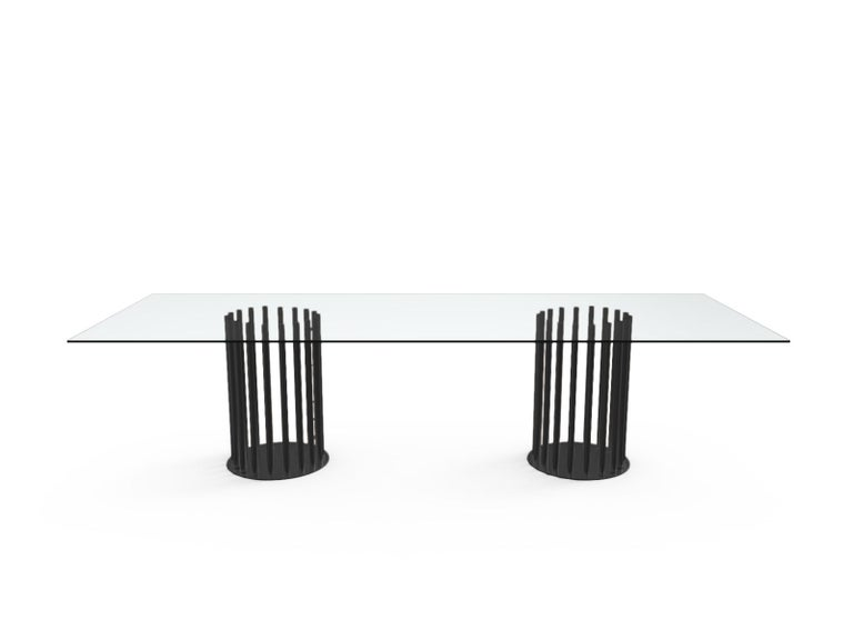 Rectangular dinner tables with extra light tempered glass top with satinated fillet in different sizes, supported by a series of light and slim metal legs, available in the following finishes in RAL colors or brass, dark bronze, satin-finish black.