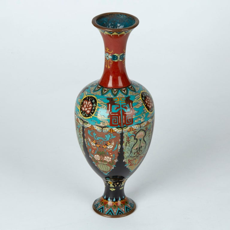 A stunning and elaborately decorated antique Japanese cloisonné vase of elegant shape standing on a narrow rounded pedestal foot with an egg shaped body and tall slender trumpet neck. The vase is decorated with in colored enamels on a blue and red