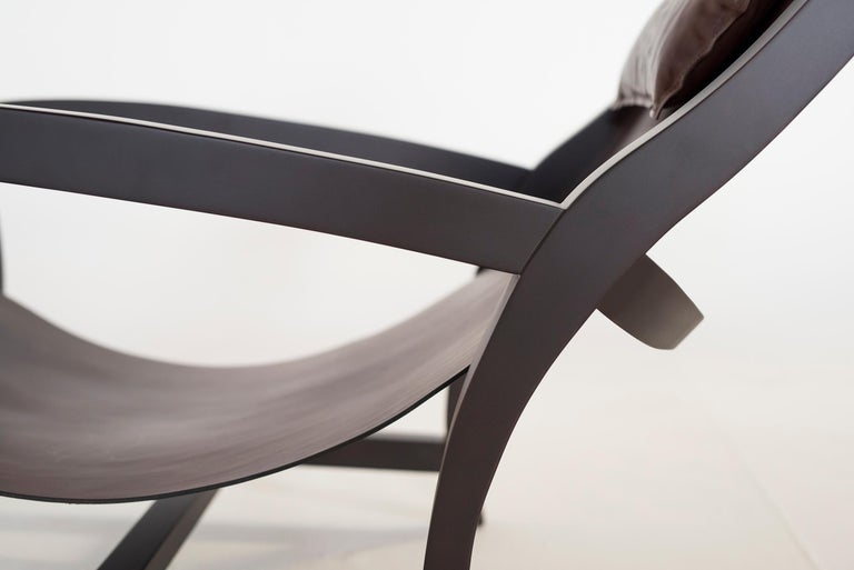 Elba is an elegant chair whose linear design conveys a sensation of lightness, while ensuring total relaxation. Inspired by the classical deckchair, its rigid structural elements are offset by a low-slung seat in select hide leather of ample