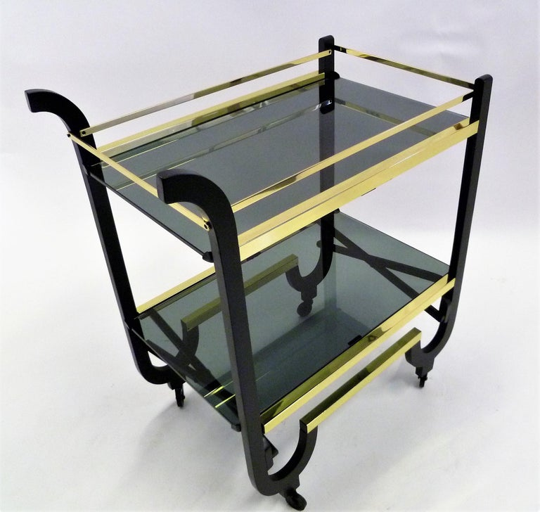 Simply elegant with its brass trims and bars, this 1940s rolling streamline moderne cart features two smoked glass surfaced shelves, Black enameled wood and when the glass shelves are removed, collapsible for storage. Brasses professionally