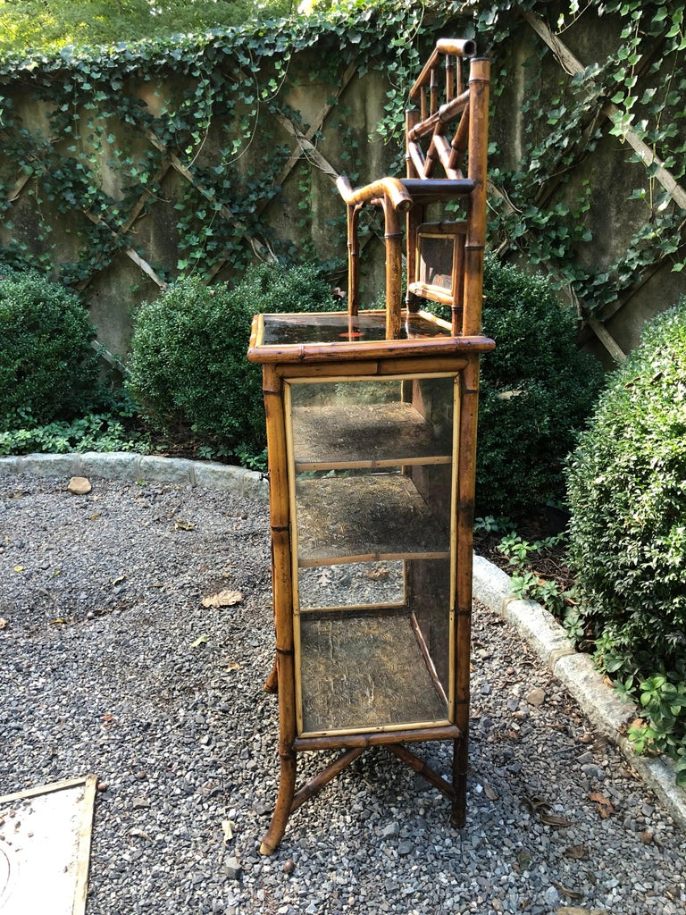 English bamboo cabinet with 3 shelves decorated with leather paper and a floral lacquered top. Glass door. All original.