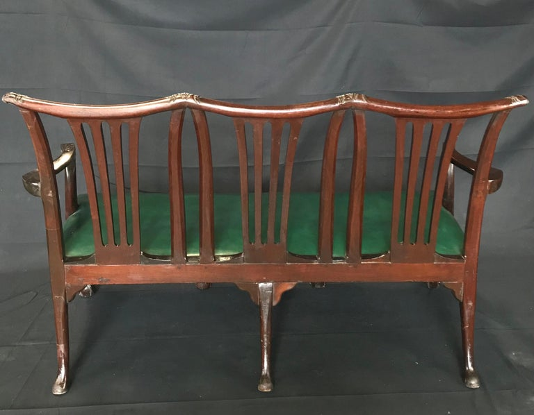 Georgian Irish style Victorian green leather sofa settee boasting beautiful triple mahogany shaped backs, elegantly shaped arms with detailed floral and scrolled carving, and hand carved hawk claw feet with meticulous detailing. The leather is