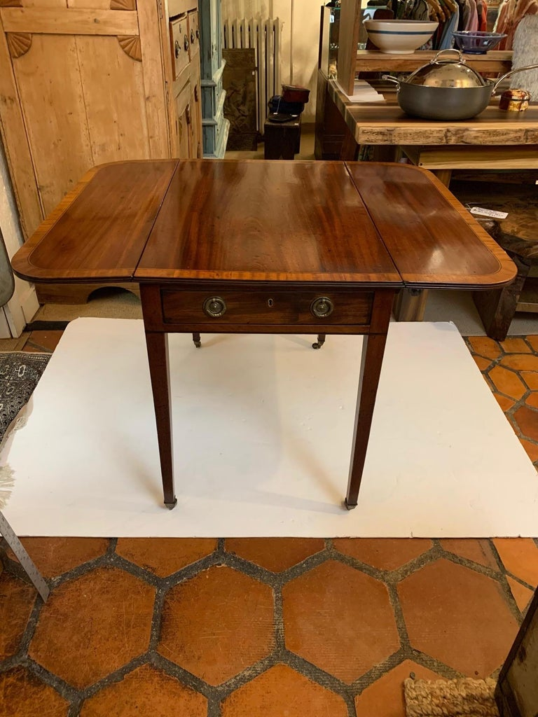 """Magnificent antique English Pembroke mahogany and satinwood inlay table having one drawer, original hardware and brass casters on tapered legs.  Fully open 40"""" wide."""