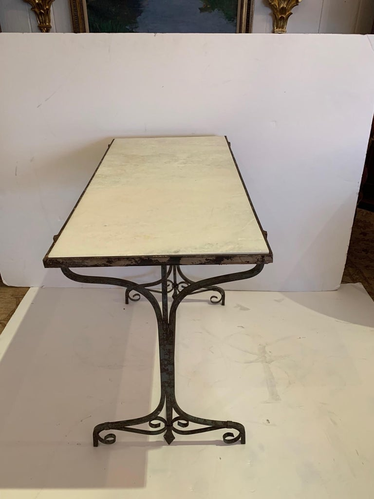 French style small bistro table or console having white marble top and elegant distressed iron base.