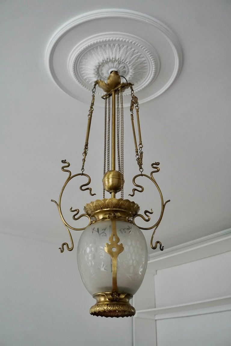 Elegant Art Deco chandelier or lantern in brass and glass. Belgium, 1900-1930.  The light requires one single E27 screw fit lightbulbs (100 Watt max.) LED compatible.  Measures: Height 95 cm. Width 44 cm. Depth 23 cm.