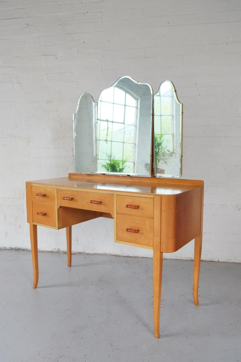 A beautiful early 1950s handmade English dressing table. The dressing table has an elegant design with curved corner details and tall slim legs, hosting five drawers. Made with a honey coloured birch wood which has a figured grain across the drawer
