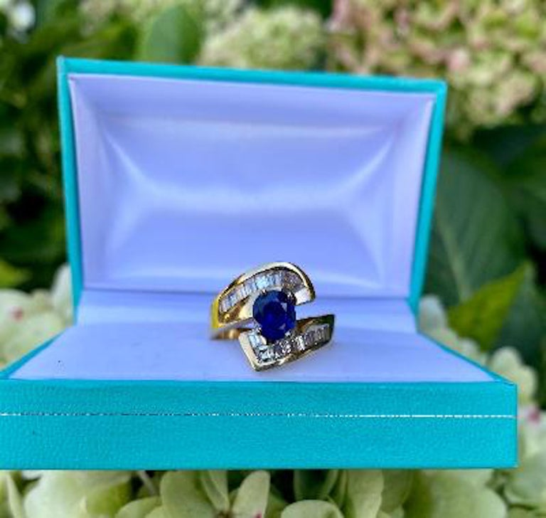 Classic bypass style 14 karat yellow gold estate ring features a vivid, cornflower blue oval shaped natural sapphire, prong set with 4 prongs, and surrounded by approximately 1.75 carats of channel set square and tapered baguette diamonds.  Sapphire