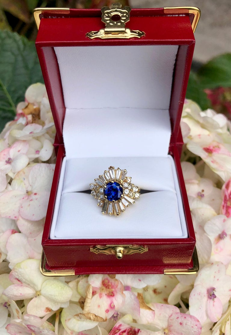 Classic ballerina style 14 karat yellow gold estate ring features a vivid, cornflower blue round blue sapphire, prong set with 6 prongs, and surrounded by 2 carats of long, prong set tapered baguettes and prong set round brilliant diamonds.