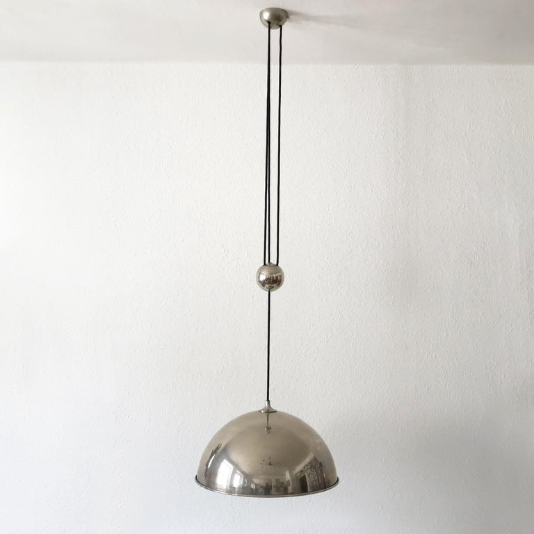 Elegant Mid-Century Modern counterweight pendant lamp by Florian Schulz, Germany, 1980s.  Executed in nickel-plated brass. The lamp needs 1 x E27 Edison screw fit bulb, is wired. It runs both on 110 / 230 Volt.   Adjustable total height (the cord is