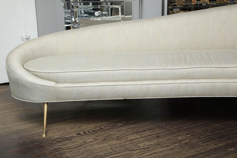 Elegant curved sofa in custom upholstery with brass legs.