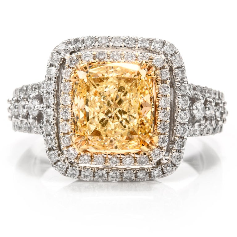 This elegant Engagement ring features a Cushion shaped natural Yellow  Diamond center and was inspired in a Double Halo design.  Crafted in 7.3 grams of 18K gold, this ring measures appx.  12.96 x 12.96 x 7.63mm High. As the focal point, contrasting