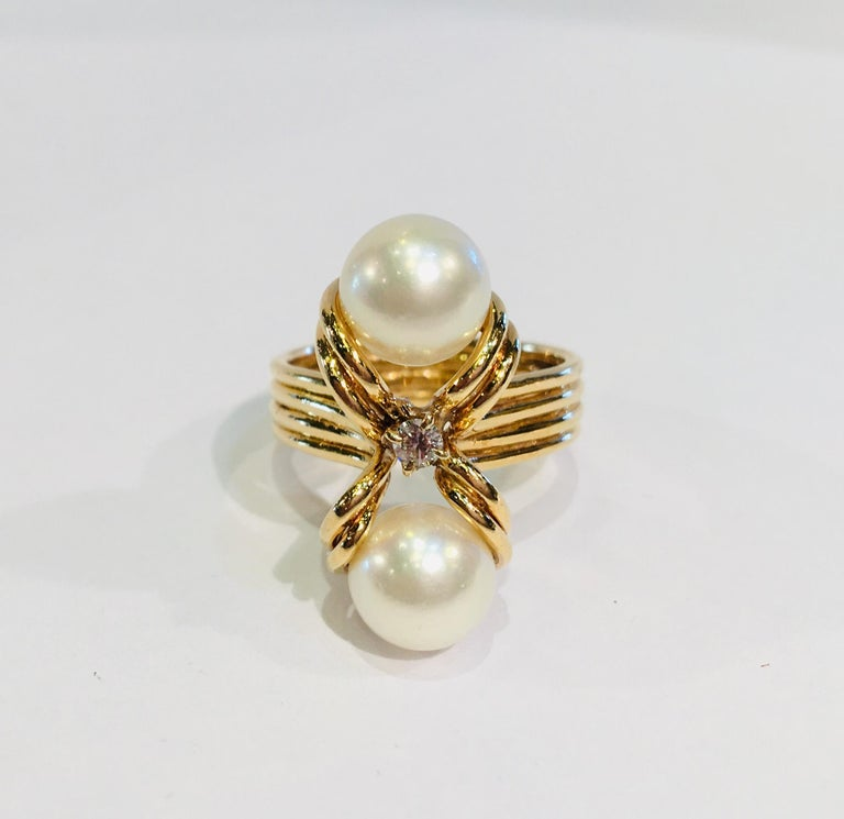 Beautifully proportioned, custom-made, 18 karat yellow gold estate ring features a pair of 2 round white cultured pearls with a beautiful luster, separated by an