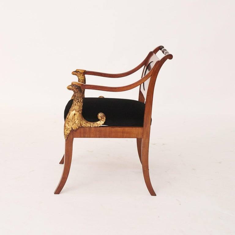 Elegant and decorative Empire armchair. Made in mahogany, with light wood inlaid (lemon tree). Oval backboard in ebonised wood. Front of arms in the form of wooden cut grippers with original gilding. Loose seat, reupholstered in black velor.
