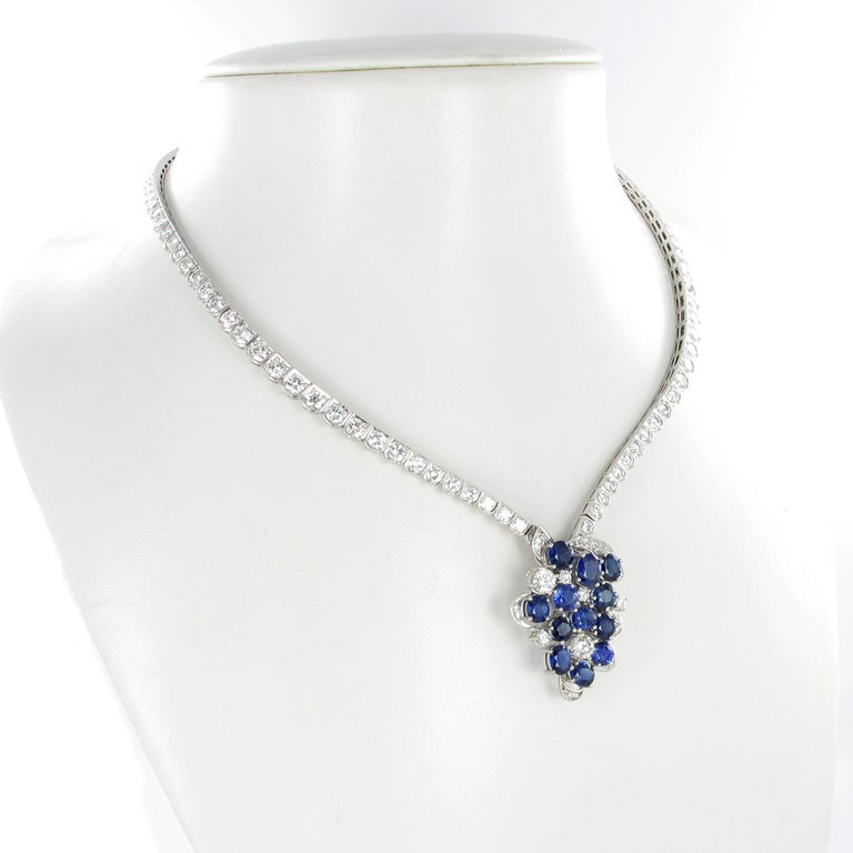 This beautiful necklace is handcrafted in 950 platinum and set with 12 oval shaped and lively colored sapphires, total weight approximately 11.00 carats. In addition, pendant and necklace are set with 135 brilliant-cut diamonds of G/H color and
