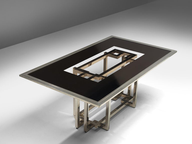 Dining table, glass and steel, Europe, 1970s  This glass and chromed dining table brings a luxurious ambiance in your interior. The table features a rectangular shaped tabletop, with a combination of darkened as outlines and smoked glass in the