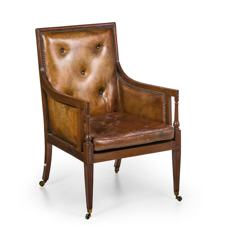 Lounge chair England Mahogany. Simple profiled frame with high backrest and armrest with column supports. Leather upholstery and leather cushions. On brass casters.