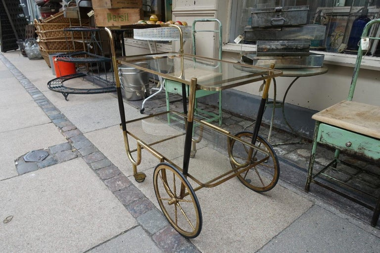 Elegant 1930s serving cart / drinks trolley, from France. Brass frame, large wheels, wooden cladding on the frame and handles. Original glass shelves. Super item and quality piece.