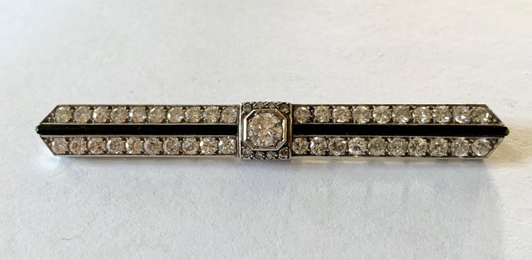 A superb and stylish  Art Deco diamond and Onyx bar pin brooch  featuring a center diamond weighting approximately 0.50 ct. Around the center diamond are approximately 2 ct of old cut diamonds and Onyx,  all set in platinum. A brooch from the early