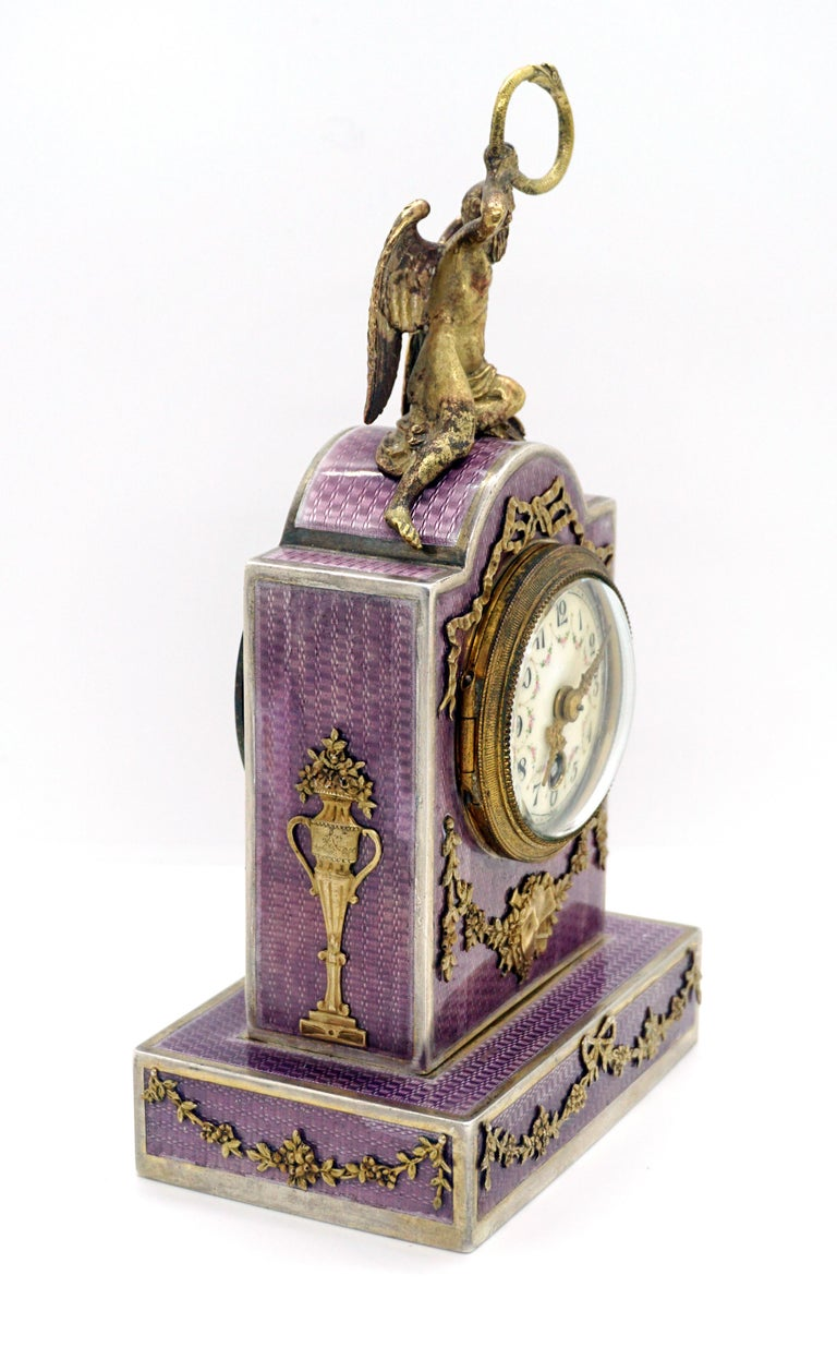 Exquisite French silver enamel table clock from the period circa 1900  Silver case with violet gouilloche enamel, porcelain dial with painted Arabic numerals, enameled floral decor and gold hands. Richly decorated with floral applications made of