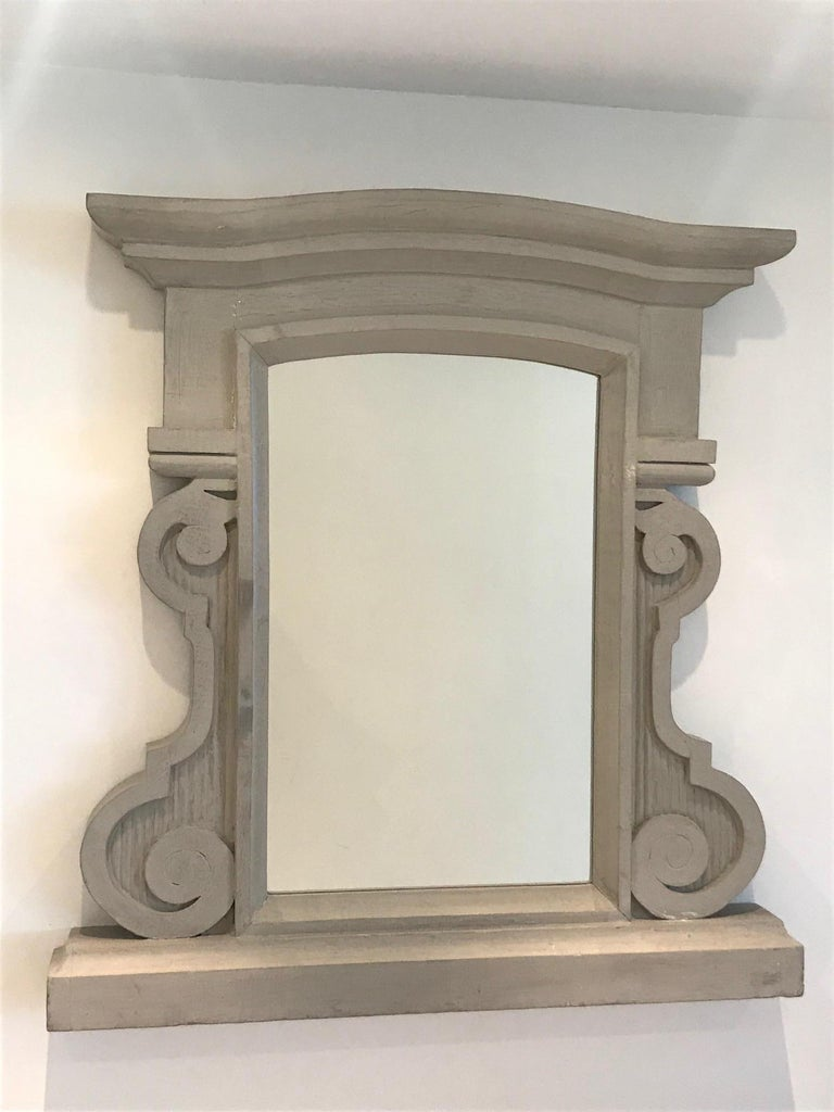 Mid-century Swedish style hand painted mirror in solid heavy weight reclaimed wood. Mirror features gorgeous hand carved frame with large chiseled scrolls and fluted details. Has curved pediment top and thick stepped shelf base. Painted in grey/tan