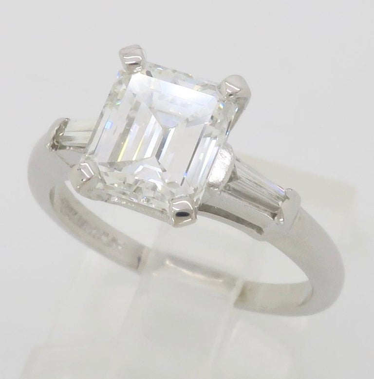 Classic GIA Certified Emerald Cut Diamond engagement ring with two tapered baguettes, made in Platinum.   GIA Certified #2211393108 Center Diamond Carat Weight: 1.75CT Center Diamond Cut: Emerald Step Cut Center Diamond Color: E Center Diamond