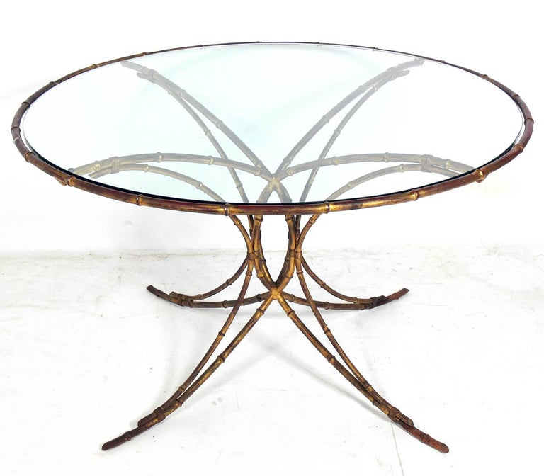 Elegant gilt metal faux bamboo dining set, probably Italian, circa 1950s. The set consists of the dining table, two armchairs and two side chairs. The dining table measures: 28.5