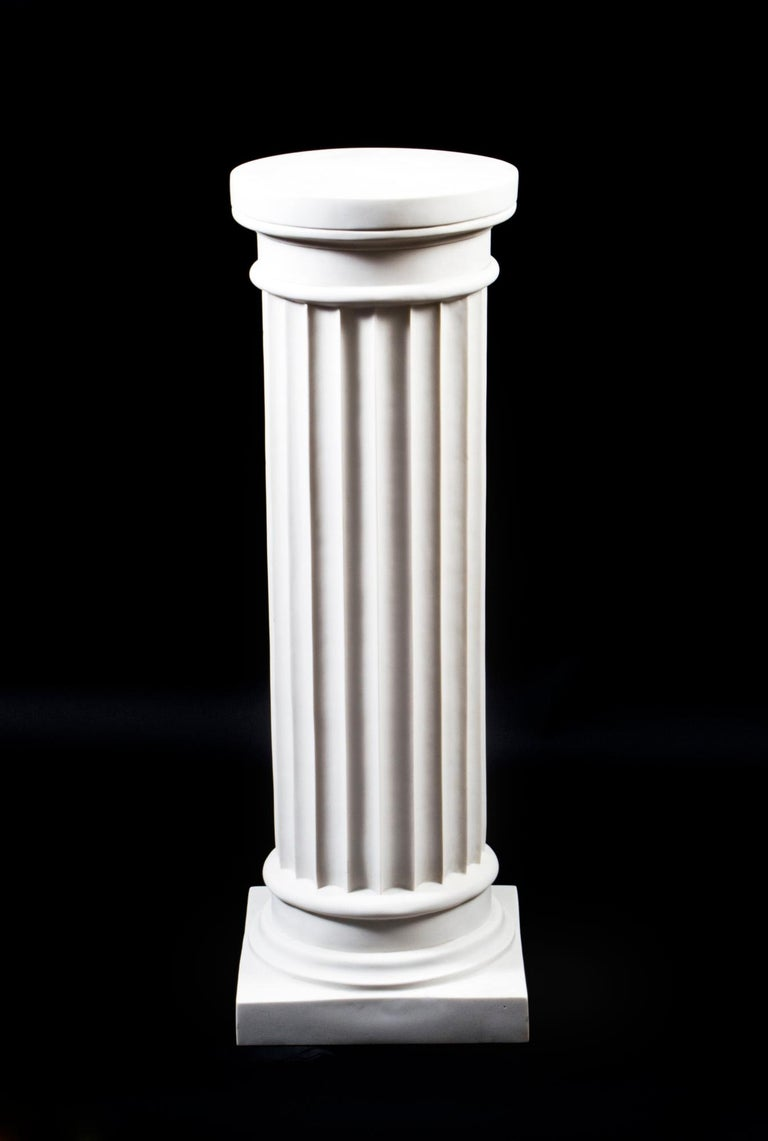 A elegant pedestal in the form of a classical ancient Greek Doric column dating from the last quarter of the 20th century.  The column has a fluted body with an plain and undecorated column capitals and tapers faintly larger in circumference