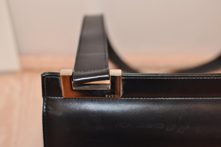 This is a black leather Gucci shoulder handbag with a single strap and silver hardware (Gucci incised one one). There is a flap snap closure at the front. Inside, the lining is black leather and there is one generous compartment; a narrow slit