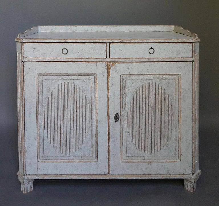 Period Gustavian sideboard, Sweden, circa 1800. Scraped back to its original surface. Two drawers over two doors with raised and reeded oval panels. Gallery top, canted corners and tapering square feet. Inside are two fixed, full-width shelves.