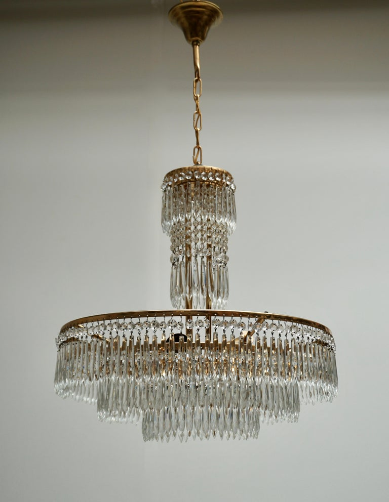 20th Century Elegant Hollywood Regency Crystal and Brass Chandelier For Sale