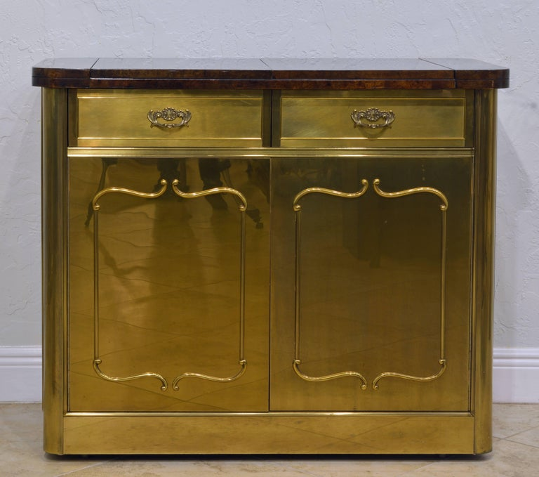 This elegant Mastercraft server features a burled wood top that flips up to both sides creating a much longer work space above two drawers and two doors opening up to a shelved interior all clad in polished and decorated brass. Concealed wheels