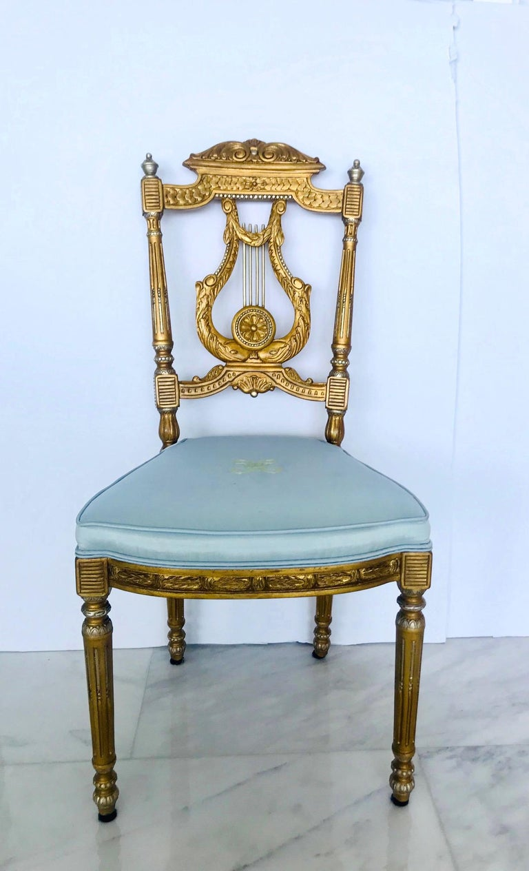 Beautiful salon chair or accent chair with neoclassical designs. Made of hand carved wood finished in antique gold leaf with silver leaf accents. The chair features a scrolled pediment top with carved ornamental designs throughout and with an