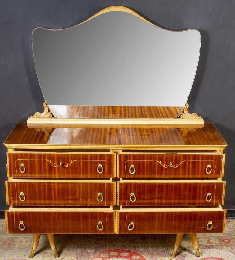 In birch and mahogany veneered with six drawers and brass handles. Available also the finely carved mirror.  Measures: Width 155 cm, height cm 88, depth cm.55 Mirror cm 130 x 90.