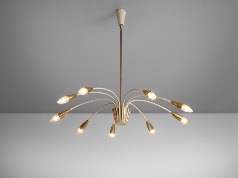 Pendant, brass, white-coated metal, glass, Italy, circa 1960s.   This brass, large nine armed biomorphic pendant is both modern and classic at the same time, a trait that Italian lights often achieve. The chandelier is delicate thanks to the sleek