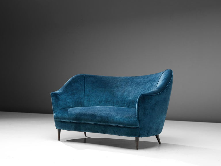 Sofa, wood and blue fabric, Italy, 1950s.  Two-seat Italian sofa in blue velvet upholstery. This sofa shows beautiful and elegant lines. The wide seating is executed with high armrests pointed up that give this settee an airy, frivolous look. The