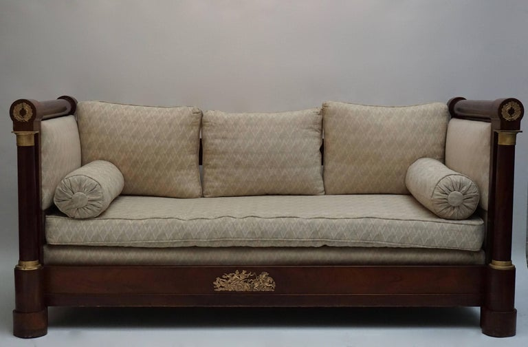 A beautiful mahogany Empire settee sofa, with paneled sides and free, standing columns up front, supporting the cylindrical armrests, upholstered. Fire, gilt bronze ornaments on the columns, frontal plinth and armrests. Continental, circa