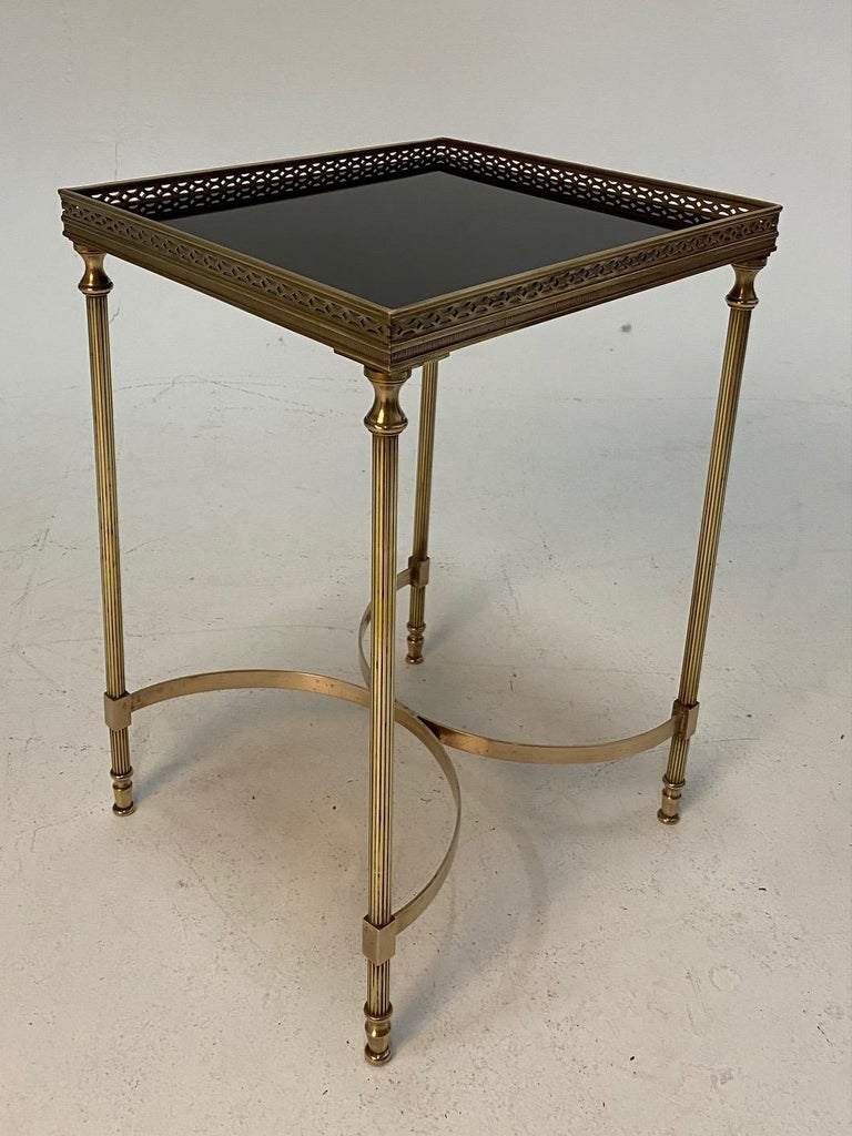 Classically elegant French Maison Jansen Hollywood Regency style cocktail end table having pierced brass gallery, tapered legs and contrasting black glass table top.
