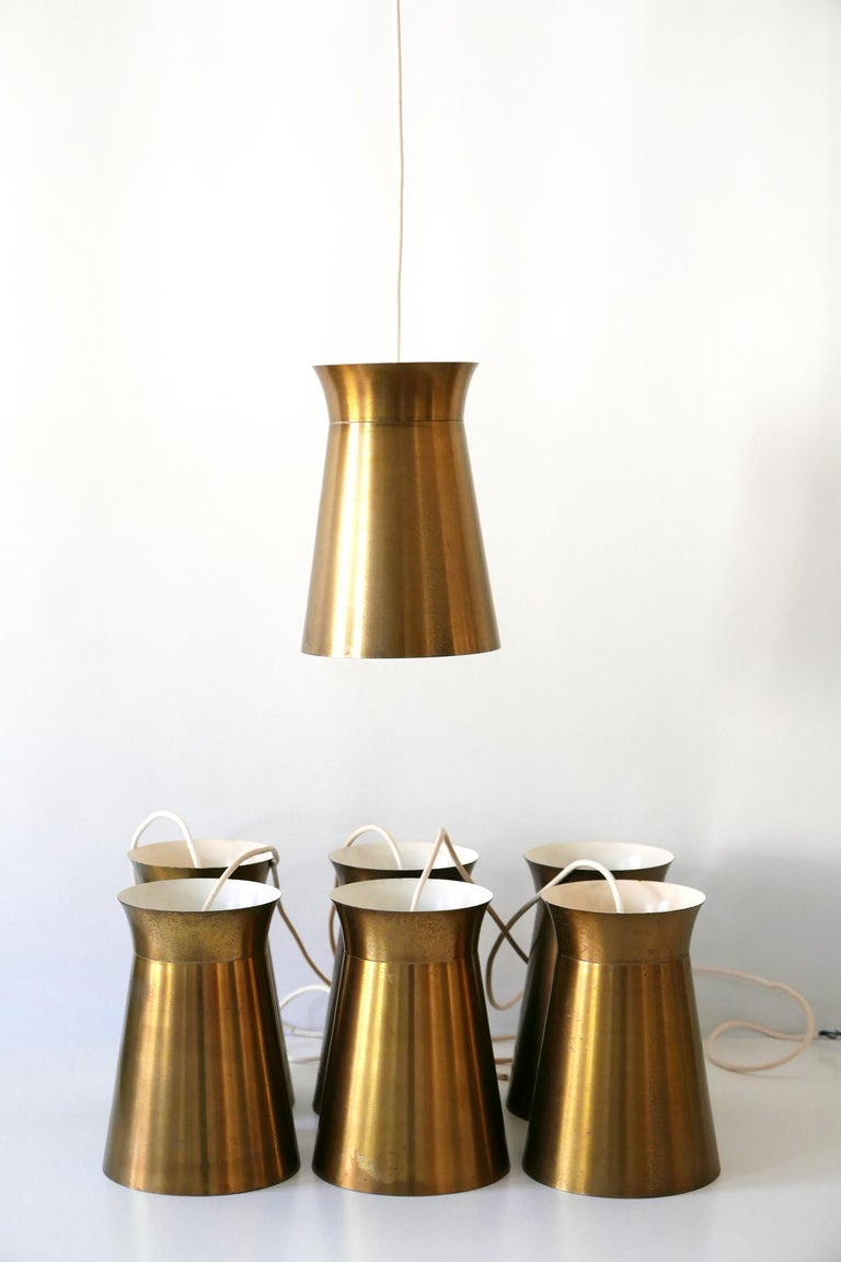 Elegant Mid-Century Modern brass pendant lamps or hanging lights. Designed and manufactured in Germany, 1950s. Seven identical lamps available!  Executed in brass sheet, each lamp comes with 1 x E27 Edison screw fit bulb holder, is wired and in