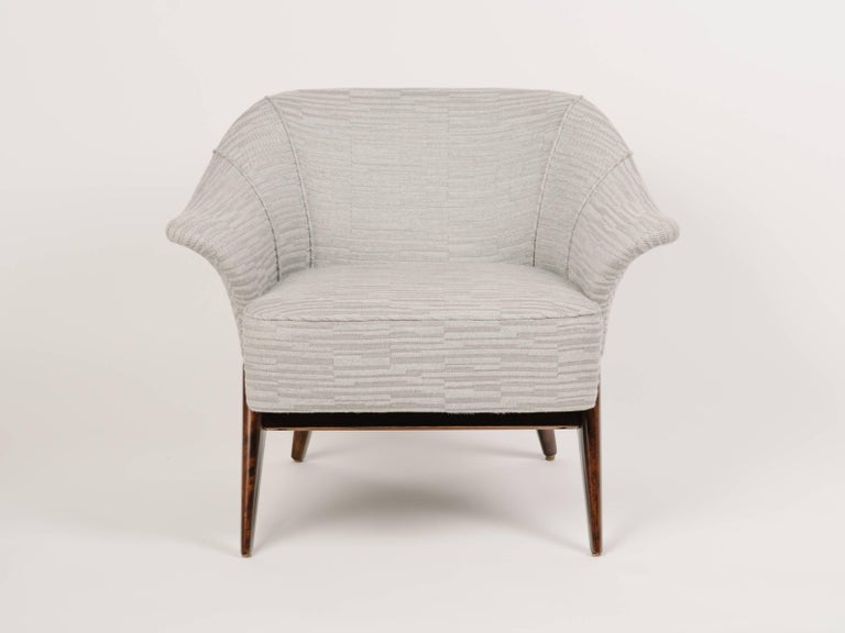 Outstanding Mid-Century Modern lounge chair with sculptural form. The chair has barrel form with winged swan sides and striking maple wood frame. Newly restored and upholstered in woven and embossed cotton-wool fabric with geometric pattern in light