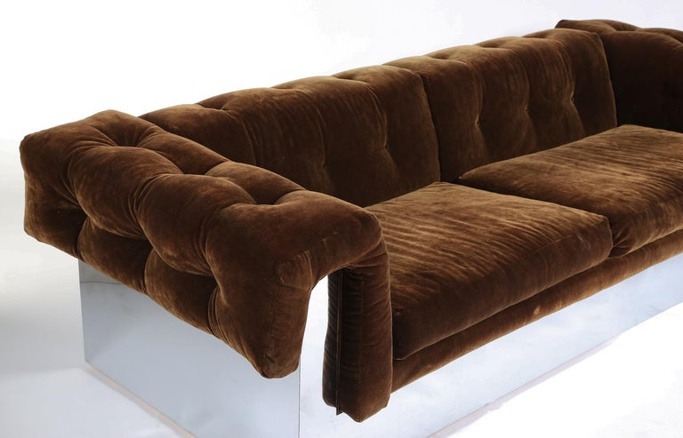 Chrome wraps entire base and forms support for the button-tufted arms and back. Elegant from every angle-his best sofa design.