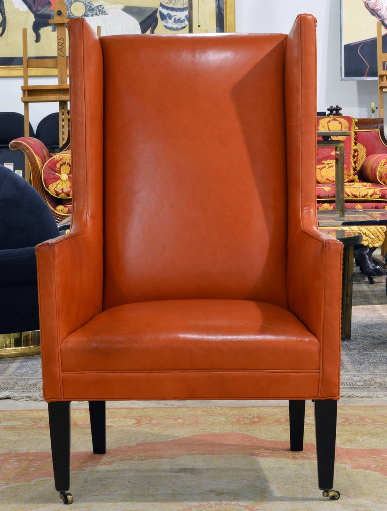 The Hermes orange color of the glove quality leather and the refined proportions and details make this chair stand out. The sides of the chair are accented by nail-head trim adding a Classic feel and the front legs rest on brass casters making