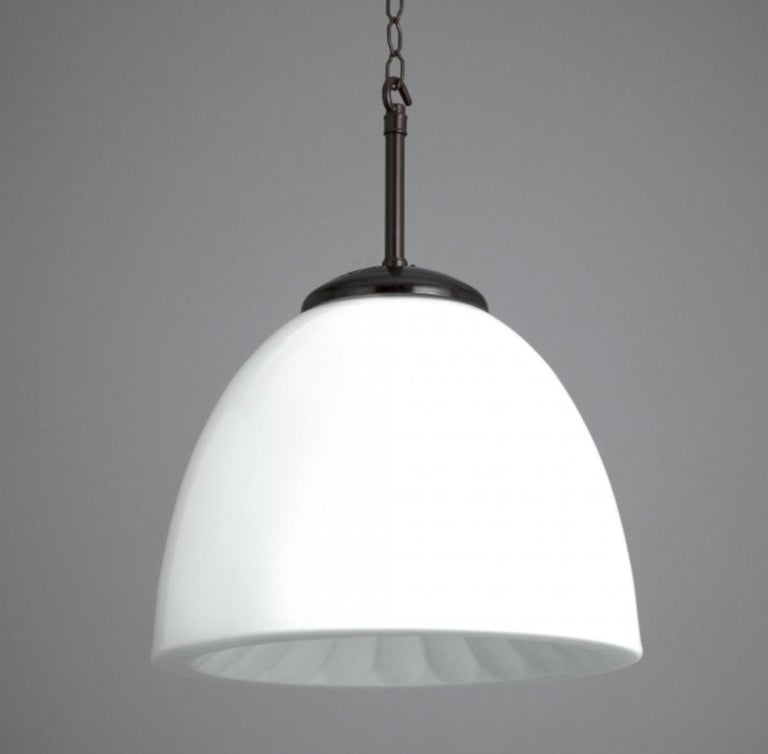 Large set elegant opaline midcentury glass pendants lights with a decorative underside and their original Bakelite galleries. The lights were salvaged from a school in the former Czechoslovakia. These make fantastic feature lights within circulation