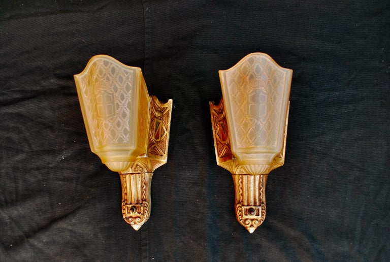 A beautiful pair of 1920s cast iron sconces, the patina is much nicer in person, the glass has a beautiful pattern, we are going to remove some of the white paint that is on the edge of the metal frame.