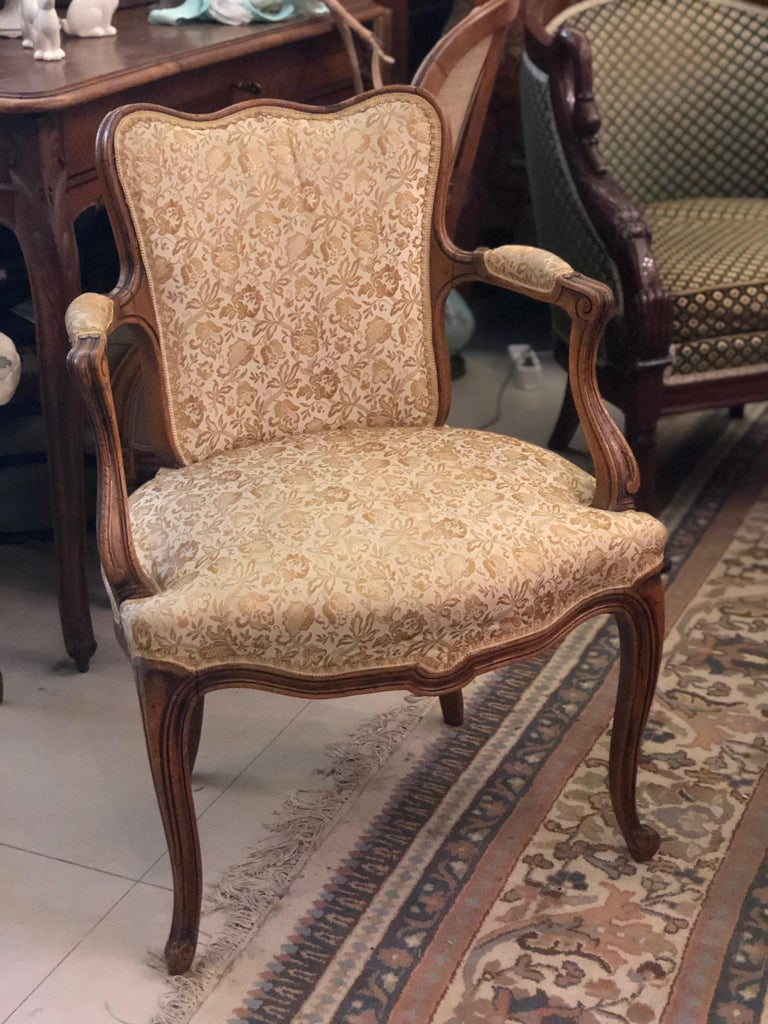 Pair of antique armchairs from France. These chairs are made of solid walnut with curved legs and back and have been reupholstered with a beige fabric with floral motifs. Very comfortable and cozy. Very good condition, France, circa 1880.